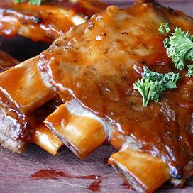 marinated ribs on a cutting board with parsley garnish