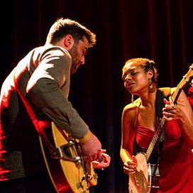 man plays guitar next to woman playing the banjo